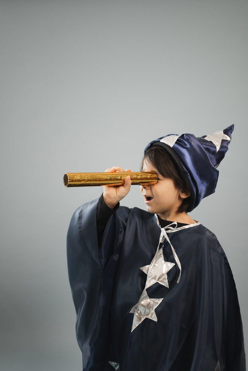 amazed boy wearing magician cape looking through kaleidoscope tube